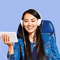 Una joven con auriculares sonriendo mientras mira su tableta.