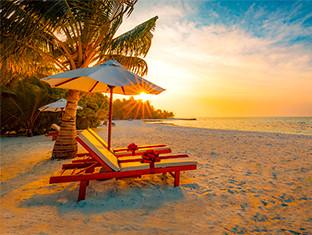 Atardecer en la playa con un sillón en la arena