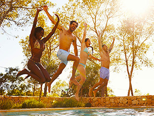 Group of friends jumping into a pool together