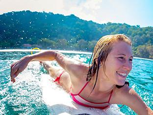 Una mujer joven sonriendo sobre una tabla de surf.