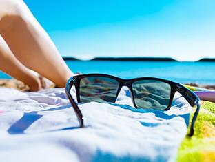 Unas gafas de sol sobre una toalla de playa con un cielo azul despejado y el mar de fondo