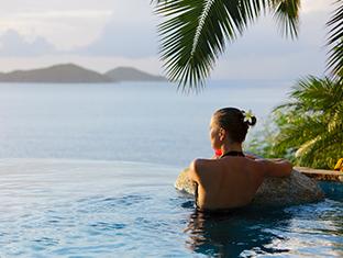 Una mujer descansando en una piscina con una hermosa vista tropical