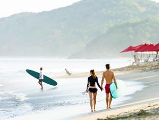 Un hombre y una mujer caminando por la playa con tablas de surf
