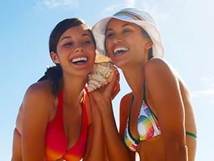 Dos mujeres jóvenes escuchando una caracola y sonriendo en la playa
