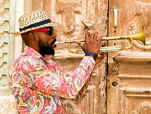 Un hombre con una camisa colorida tocando la trompeta.