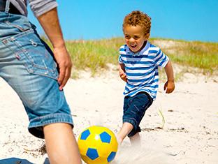 ¡Un niño divirtiéndose mientras juega al fútbol en la playa!