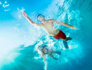 Una toma bajo el agua de dos niños nadando en el mar.