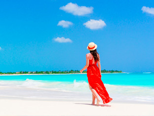A brunette woman wearing a bright red dress and sun hat walking along the beach.