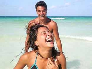 Un hombre y una mujerdivirtiéndose en la playa.