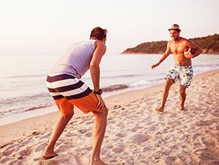 Dos muchachos en la playa jugando al fútbol americano
