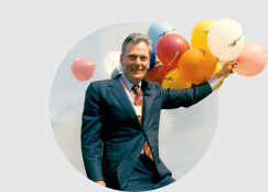 Herb Kelleher holding a large bunch of Southwest Airlines balloons
