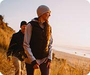 un hombre y una mujer practicando excursionismo junto a la playa