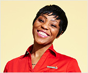An African American woman with a short pixie cut wearing a vibrant red Southwest Airlines polo shirt smiling brightly against a pastel yellow backdrop.