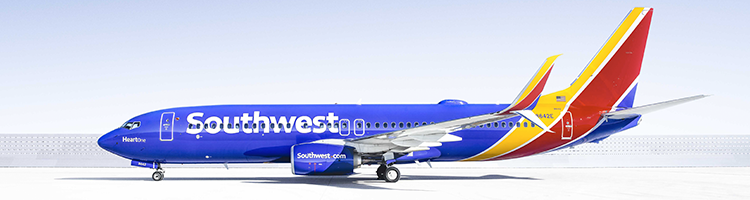 A majestic Southwest Airlines 737 sits on a bright, sun-lit runway while awaiting takeoff.