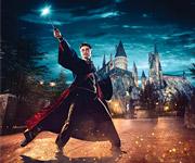 Harry Potter sosteniendo su varita frente al Colegio Hogwarts.