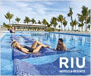 Una pareja descansando en la piscina de un lujoso complejo hotelero RIU.