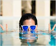 Una joven con gafas de sol en la piscina de un complejo hotelero haciendo el símbolo de la paz con ambas manos.