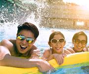 Un padre asiático con sus dos hijas sonriendo dentro de la piscina de un complejo hotelero.