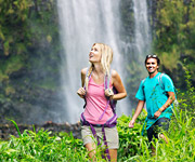 Un hombre y una mujer viajando de mochileros frente a una cascada.