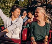Amigos sonriendo risueños en una montaña rusa