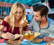 Hombre y mujer jóvenes sonriendo mientras comen tacos