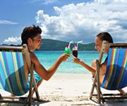 Un hombre y una mujer brindando mientras descansan sentados en la playa.