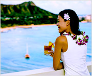 A young lady wearing lei and a flower in her hair overlooking the ocean with Diamon Head in the background.