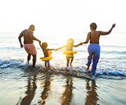 Una familia en la playa metiéndose en el agua