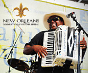 Man playing piano accordian with a New Orleans logo in the top left corner