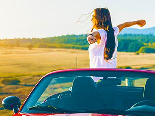 Woman with arms outstretched looking outside of her rental car